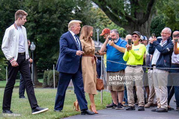 US President Donald Trump talks to White House workers and contractors as he returns to the White House with First Lady Melania Trump and their son...