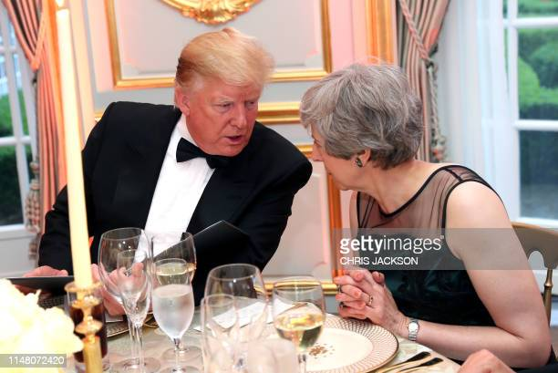 President Donald Trump talks with Britain's Prime Minister Theresa May during a dinner at Winfield House the residence of the US Ambassador where US...