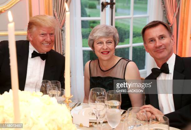 US President Donald Trump talks with Britain's Prime Minister Theresa May and Britain's Foreign Secretary Jeremy Hunt during a dinner at Winfield...