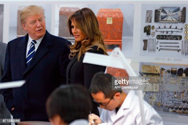 US President Donald Trump talks with First Lady Melania Trump as they tour the Conservation Scientific Laboratory of the Forbidden City in Beijing on...