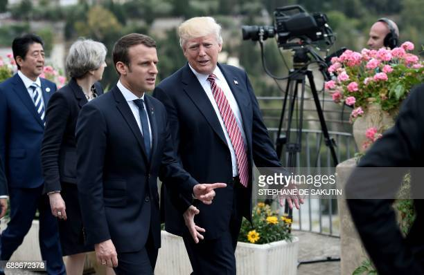 US President Donald Trump talks with French President Emmanuel Macron as they attend the Summit of the Heads of State and of Government of the G7 the...