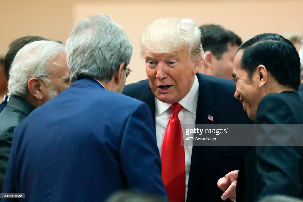 US President Donald Trump (C) talks with India's Prime Minister Narendra Modi (L), Italy's Prime Minister Paolo Gentiloni (2nd L) and Indonesia's President Joko Widodo prior to a working session during the G20 summit in Hamburg, northern Germany, on July 8, 2017. Leaders of the world's top economies gather from July 7 to 8, 2017 in Germany for likely the stormiest G20 summit in years, with disagreements ranging from wars to climate change and global trade. / AFP PHOTO / POOL / Markus Schreiber
