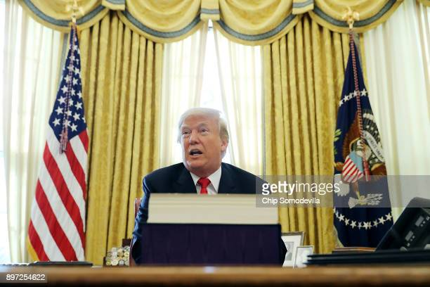 S President Donald Trump talks with journalists after signing tax reform legislation into law in the Oval Office December 22 2017 in Washington DC...