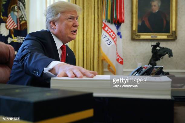 S President Donald Trump talks with journalists before signing tax reform legislation into law in the Oval Office December 22 2017 in Washington DC...