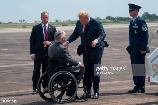 US President Donald Trump talks with Texas Governor Greg Abbott as he arrives at Ellington Field Joint Reserve Base in Houston Texas on May 31 2018