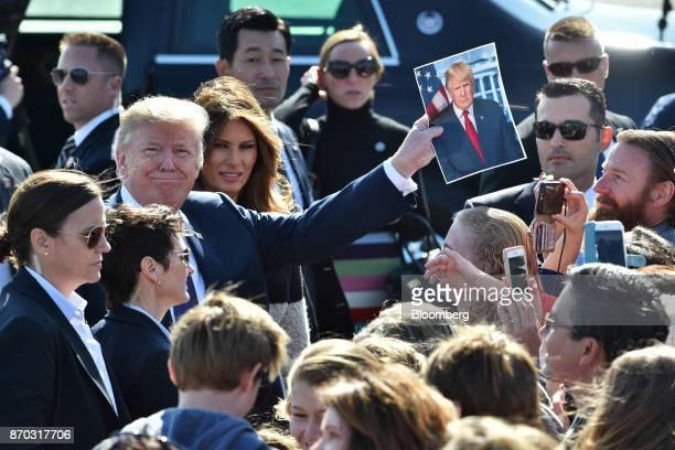 US President Donald Trump third left holds a photograph of himself while US First Lady Melania Trump fourth left looks on as they greet attendees...