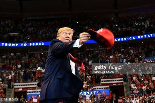 US President Donald Trump throughs MAGA caps to supporters as he arrives for a Keep America Great campaign rally at the BBT Center in Sunrise Florida...