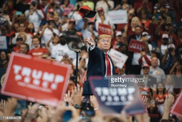 US President Donald Trump throws a hat to the crowd during a 'Homecoming' rally in Sunrise Florida US on Tuesday Nov 26 2019 Trump is preparing to...