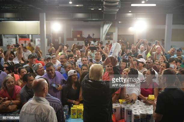 US President Donald Trump throws a paper towel roll as he visits the Cavalry Chapel in Guaynabo Puerto Rico on October 3 2017 Nearly two weeks after...
