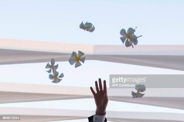 US President Donald Trump throws flowers during their visit to the USS Arizona Memorial on November 3 at Pearl Harbor in Honolulu Hawaii / AFP PHOTO...
