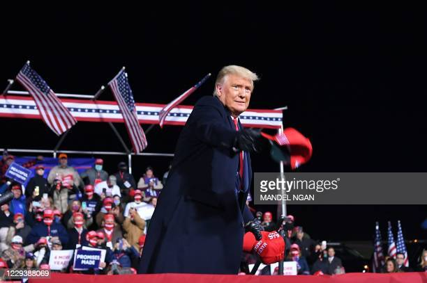 President Donald Trump throws MAGA hats to supporters during a rally at Williamsport Regional Airport in Montoursville, Pennsylvania on October 31,...