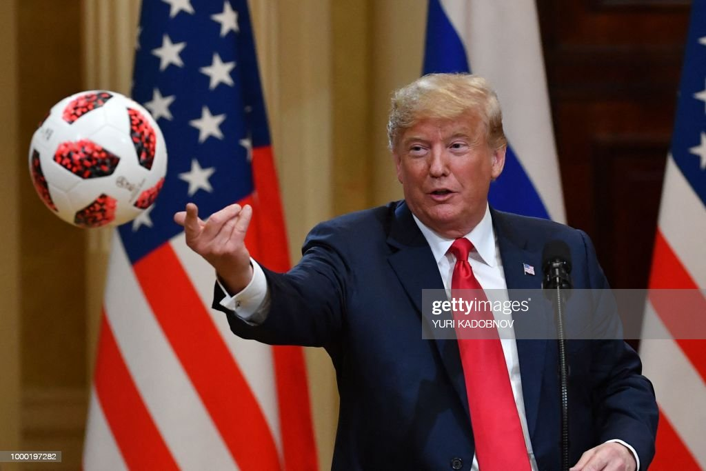 President Donald Trump throws to his wife (unseen) a ball of the 2018 football World Cup that he received from Russia's President as a present during a joint press conference after a meeting at the Presidential Palace in Helsinki, on July 16, 2018. - The US and Russian leaders opened an historic summit in Helsinki, with Donald Trump promising an 'extraordinary relationship' and Vladimir Putin saying it was high time to thrash out disputes around the world.