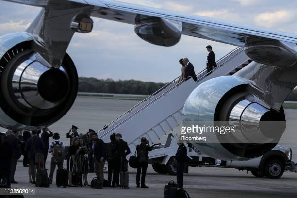 US President Donald Trump top center waves as he walks with US First Lady Melania Trump and son Barron Trump as he arrives aboard Air Force One in...