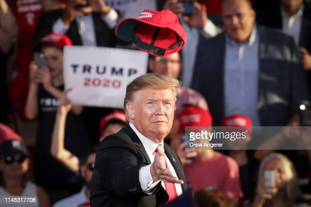 S President Donald Trump tosses a hat into the crowd as he arrives for a 'Make America Great Again' campaign rally at Williamsport Regional Airport...