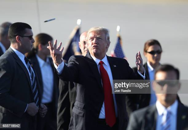 President Donald Trump tosses a sharpie pen that he was using for autographs back to the group that greeted him after arriving on Air Force One at...