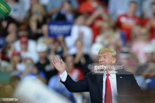 S President Donald Trump tosses hats to the crowd at a campaign rally at the Ford Center on August 30 2018 in Evansville Indiana The president was in...