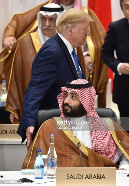 US President Donald Trump touches shoulder of Saudi Arabia's crown prince Mohammed Bin Salman as he attends session 3 on women's workforce...