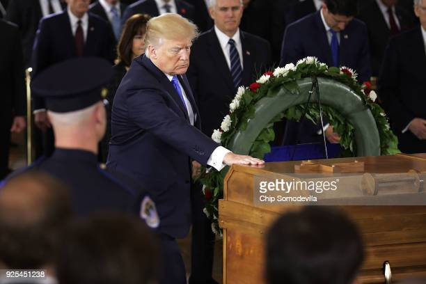 S President Donald Trump touches the casket of Christian evangelist and Southern Baptist minister Billy Graham as he lies in honor in the US Capitol...