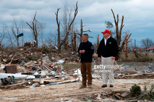 US President Donald Trump tours an area damaged in a tornado with Putnam County Rescue Squad member Mike Herrick in Cookeville Tennessee on March 6...