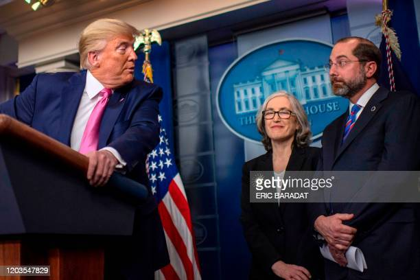 President Donald Trump turns to address US Secretary of Health Alex Azar as he speaks during a news conference on the COVID-19 outbreak at the White...