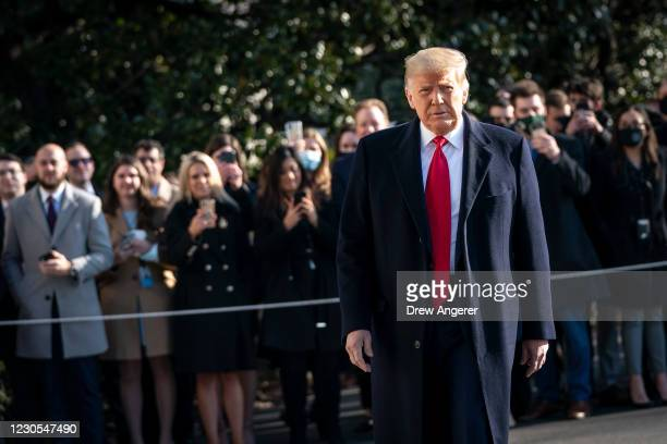 President Donald Trump turns to reporters as he exits the White House to walk toward Marine One on the South Lawn on January 12, 2021 in Washington,...