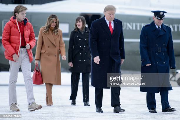 US President Donald Trump US first lady Melania Trump and son Barron Trump walk the snowy tarmac to Air Force One at Andrews Air Force Base February...
