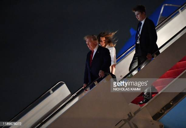 US President Donald Trump US First Lady Melania Trump and son Barron Trump arrive at Palm Beach International Airport in West Palm Beach on December...