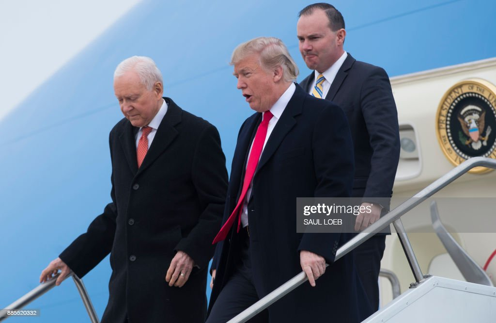 US President Donald Trump, US Senator Orrin Hatch (L), Republican of Utah, and US Senator Mike Lee (R), Republican of Utah, as they disembark from Air Force One upon arrival at Salt Lake City International Airport in Utah, December 4, 2017. /