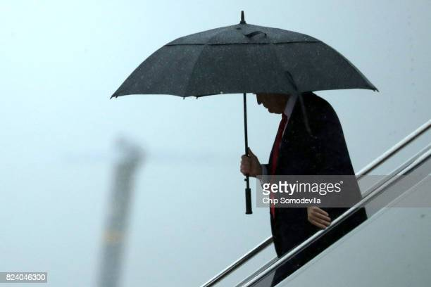 S President Donald Trump uses an umbrella after stepping out of Air Force One July 28 2017 in Joint Base Andrews Maryland Trump announced via Twitter...