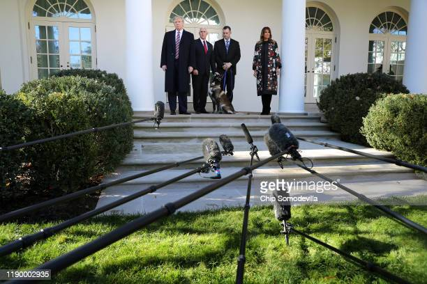 President Donald Trump, Vice President Mike Pence, an unidentified dog handler and first lady Melania Trump pose for photographs with Conan, the U.S....