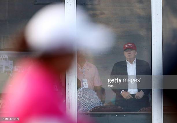 S President Donald Trump waches Shanshan Feng of China on the 16th tee during the US Women's Open round three on July 15 2017 at Trump National Golf...