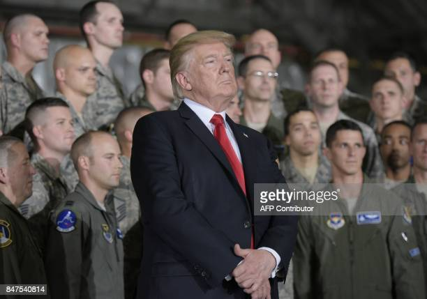 US President Donald Trump waits as he is introduced by First Lady Melania Trump before his address to military personnel and families at Andrews Air...