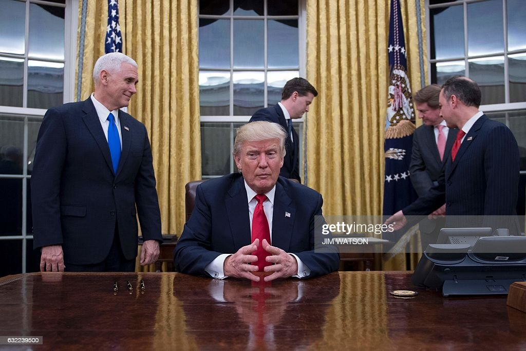 US President Donald Trump (C) waits at his desk before signing confirmations for James Mattis as US Secretary of Defense and John Kelly as US Secretary of Homeland Security, as Vice President Mike Pence (L) and White House Chief of Staff Reince Priebus (R) look on, in the Oval Office of the White House in Washington, DC, January 20, 2017. / AFP / JIM