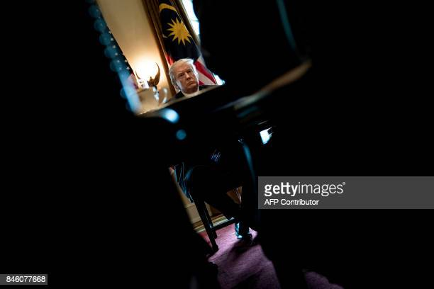 President Donald Trump waits for a meeting with Prime Minister of Malaysia Najib Razak and others in the Cabinet Room of the White House September 12...
