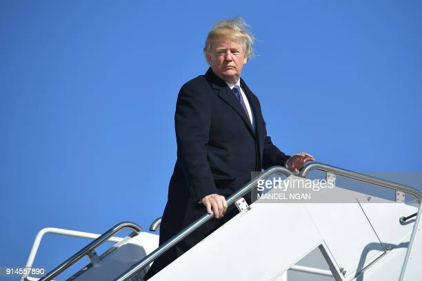 US President Donald Trump waits for his wife Melania as he boards Air Force 1 on his way to Cincinnati Ohio at Andrews Air Force Base outside...