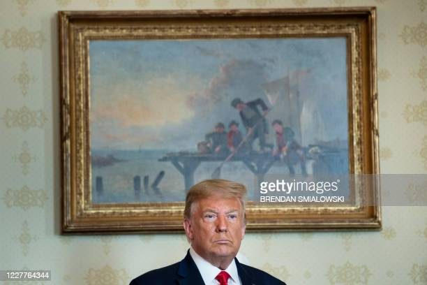 President Donald Trump waits to award former Congressman and Olympic runner Jim Ryun the Presidential Medial of Freedom during a ceremony in the Blue...