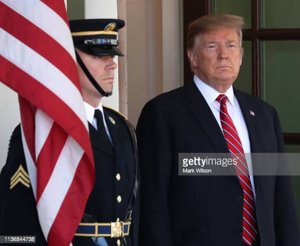 S President Donald Trump waits to greet Brazilian President Jair Bolsonaro at the West Wing of the White House March 19 2019 in Washington DC...