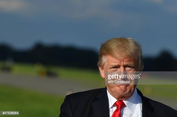 US President Donald Trump walks across the tarmac after stepping off Air Force One upon arrival at Morristown Municipal Airport in Morristown New...