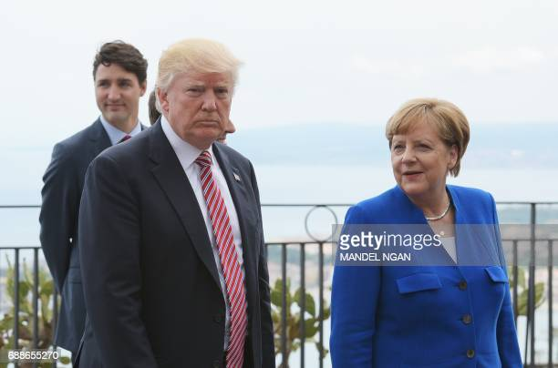 US President Donald Trump walks alonf with German Chancellor Angela Merkel at the Belvedere of Taormina during the Summit of the Heads of State and...
