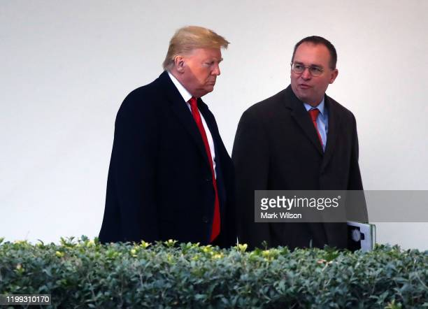S President Donald Trump walks along the West Wing Colonnade with acting White House chief of staffMick Mulvaney before departing from the White...