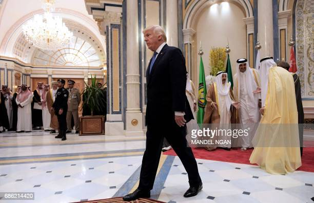 US President Donald Trump walks away after posing for a group picture with leaders of the Gulf Cooperation Council in Riyadh on May 21 2017 / AFP...