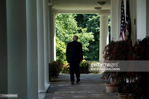 US President Donald Trump walks back to the Oval Office after speaking about immigration in the Rose Garden of the White House May 16 in Washington...