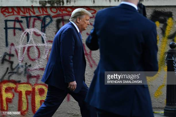 US President Donald Trump walks back to the White House escorted by the Secret Service after appearing outside of St John's Episcopal church across...