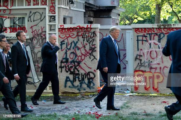 President Donald Trump walks back to the White House escorted by the Secret Service after appearing outside of St John's Episcopal church across...