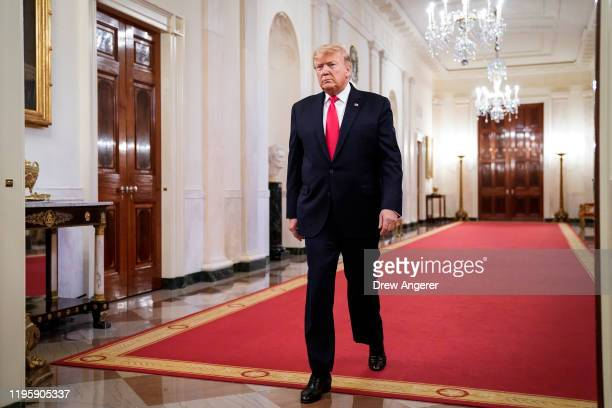 President Donald Trump walks down the Cross Hall toward East Room of the White House for an event with U.S. Mayors on January 24, 2020 in Washington,...