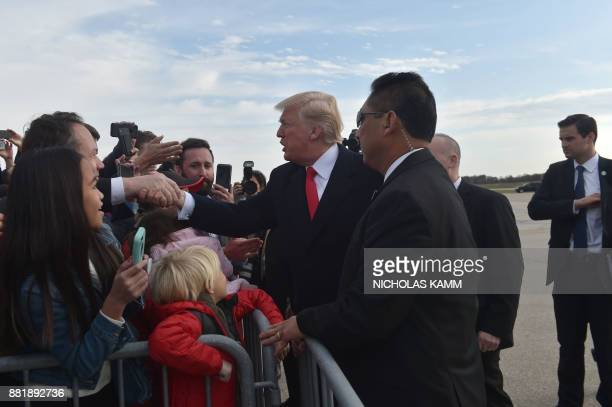 US President Donald Trump walks from Air Force One as he arrives at St Louis Lambert International Airport in St Louis Missouri to speak on tax...