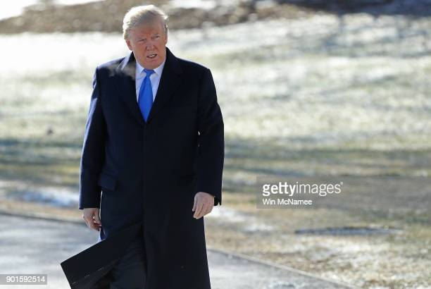 S President Donald Trump walks from the Oval Office to speak with members of the press while departing the White House January 5 2018 in Washington...