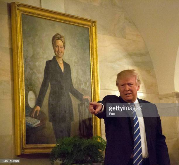 S President Donald Trump walks in a corridor of the White House to greet visitors while a portrait of Hillary Clinton hangs on the wall March 7 2017...