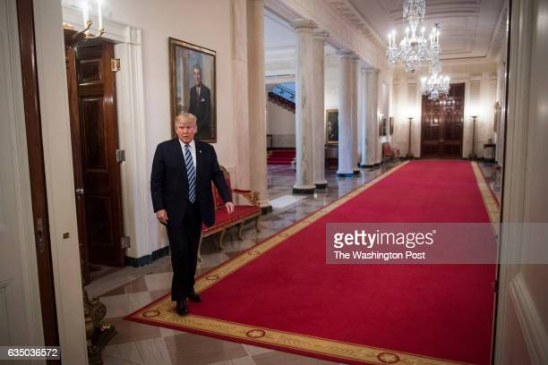 President Donald Trump walks into the Cross Hall before speaking during a meeting with airline executives in the State Dining Room of the White House...