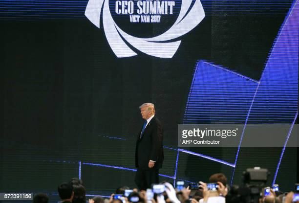 US President Donald Trump walks on the stage on the final day of the APEC CEO Summit part of the broader AsiaPacific Economic Cooperation leaders'...
